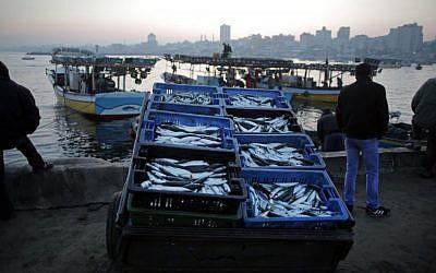 Palestinian fishermen prepare fish for sale after a night long fishing trip, in Gaza seaport , Monday, April 4, 2016. (AP/ Khalil Hamra)