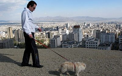 Illustrative: An Iranian man walks with his dog while spending a weekend holiday in Tochal north of Tehran, Iran, on Friday April, 10, 2009. (AP photo/Hasan Sarbakhshian)