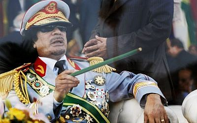 Libyan leader Moammar Gadhafi gestures with a green cane as he takes his seat behind bulletproof glass for a military parade in Green Square, Tripoli, Libya on Tuesday, Sept. 1, 2009 (AP Photo/Ben Curtis, File)