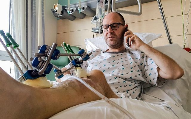 Brussels bombing survivor Walter Benjamin makes a phone call as he rests in his bed in Jette University Hospital in the city on Sunday, April 3, 2016 (AP Photo/Helene Franchineau)