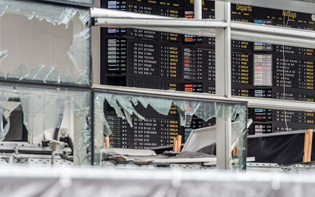 An arrivals and departure board is seen behind blown out windows at Zaventem Airport in Brussels, March 23, 2016. (AP/Geert Vanden Wijngaert, Pool)