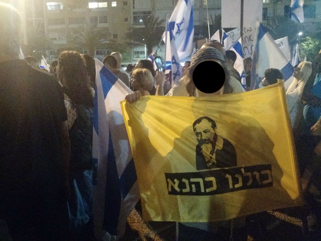 """A teen holds up a flag which reads """"We are all Kahane"""" at a protest in support of a soldier charged with manslaughter in Tel Aviv's Rabin Square on April 19, 2016. (Judah Ari Gross/Times of Israel staff)"""