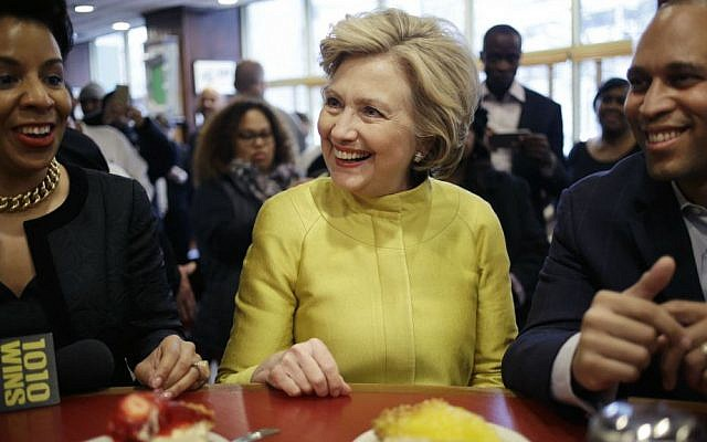 Democratic presidential candidate Hillary Clinton, center, talks with Rep. Hakeem Jeffries, D-New York, right, and Council Member Laurie Cumbo as she sits at the counter of Junior's restaurant in the Brooklyn borough of New York, Saturday, April 9, 2016. (AP Photo/Seth Wenig)