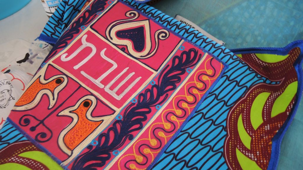 The challah covers combine traditional Ghanaian fabrics and symbols with Hebrew. (Melanie Lidman/Times of Israel)