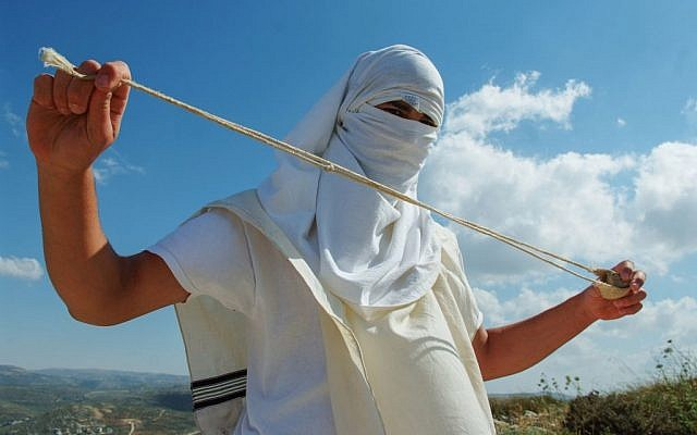 Illustrative photo of a masked Jewish settler holding a slingshot as he stands near the West Bank Jewish settlement of Mitzpeh Yitzhar, on May 19, 2013. (Mendy Hechtman/Flash90)