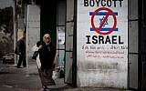 A Palestinian woman walks by a sign calling for a boycott of Israel in the West Bank city of Bethlehem on February 11, 2015. (Miriam Alster/Flash 90)