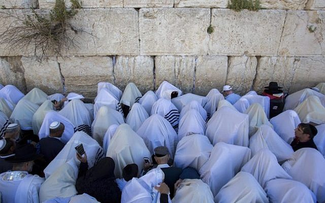 Jewish worshippers cover themselves with prayer shawls as they pray in front of the Western Wall, in Jerusalem's Old City, during the Jewish holiday of Passover on April 6, 2015. (Yonatan Sindel/Flash90)