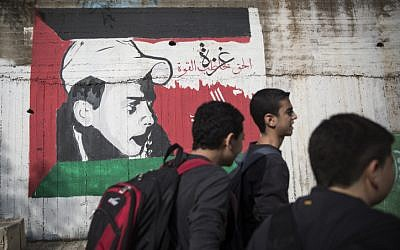Kids seen walking home after school past a graffiti painting of Muhammed Abu Khdeir, the Palestinian child killed by Jewish extremists, with the Palestinian flag, on a central street in the Northern Arab-Israel. (Hadas Parush/Flash90)