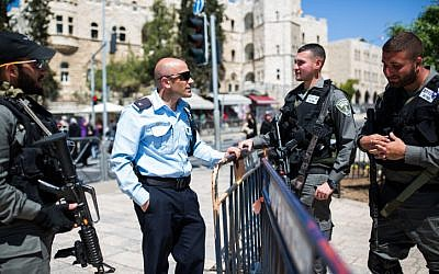 Illustrative: A policeman speak to soldiers at Damascus Gate in the Old City of Jerusalem on March 23, 2016. (Corinna Kern/Flash90)