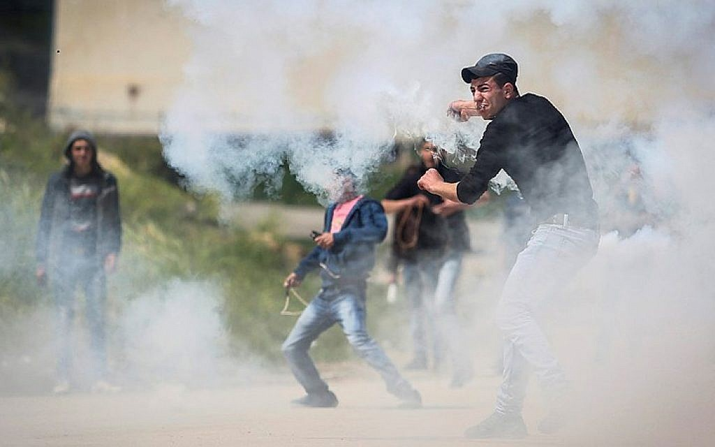 Palestinians protest in front of Israeli security forces as they mark Land Day outside the compound of the Israeli-run Ofer prison near Betunia in the West Bank on March 30, 2016. (Flash90)