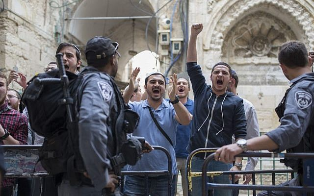Police hold back right-wing Jewish activists at the entrance to the Temple Mount compound, holy to both Islam and Judaism, in Jerusalem's Old City, on April 10, 2016. (Corina Kern/Flash90)