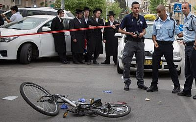Police at the scene of an accident where a public bus hit and killed a young boy who was riding his bicycle in Jerusalem on April 10, 2016 (Yonatan Sindel/Flash90)