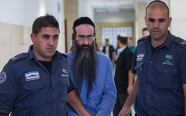 Yishai Schlissel, center, is led out of the courtroom at the Jerusalem District Court, April 19, 2016. (Yonatan Sindel/Flash90)