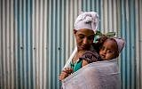 A member of the Falashmura Jewish Ethiopian community carries her baby on her back before attending the Passover prayer service, in the synagogue in Gondar, Ethiopia. April 22, 2016. (Miriam Alster/FLASH90)
