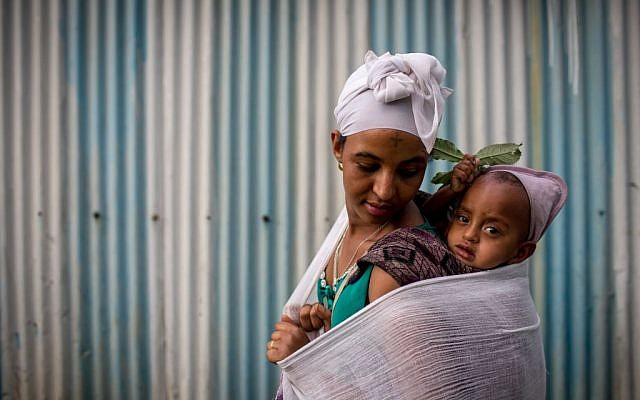 A member of the Falash Mura Jewish Ethiopian community carries her baby on her back before attending the Passover prayer service, in the synagogue in Gonder, Ethiopia. April 22, 2016. (Miriam Alster/FLASH90)