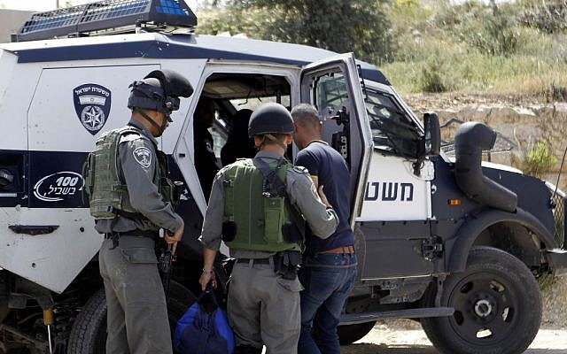 Israeli border police detain a Palestinian man near Hebron on 24 April 2016. (Wisam Hashlamoun/Flash90)