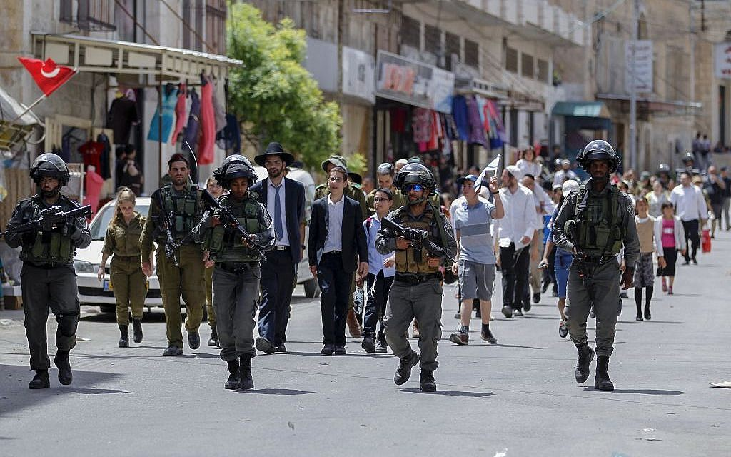 Israeli security forces guard Orthodox Jews visiting the divided West Bank city of Hebron for Passover, on April 26, 2016. (Photo by Wisam Hashlamoun/Flash90)