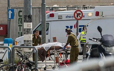 Israeli army paramedics evacuate the body of a Palestinian man at the Qalandiya Checkpoint after an attempted stabbing attack, on April 27, 2016. (Yonatan Sindel/Flash90)