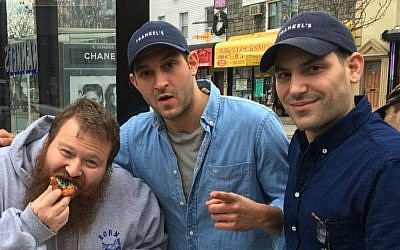 Rapper Action Bronson, left, chowing down on some Frankel's fare with the Frankel brothers, Zach, right, and Alex in front of their New York deli. (Screenshot from Instagram/via JTA)