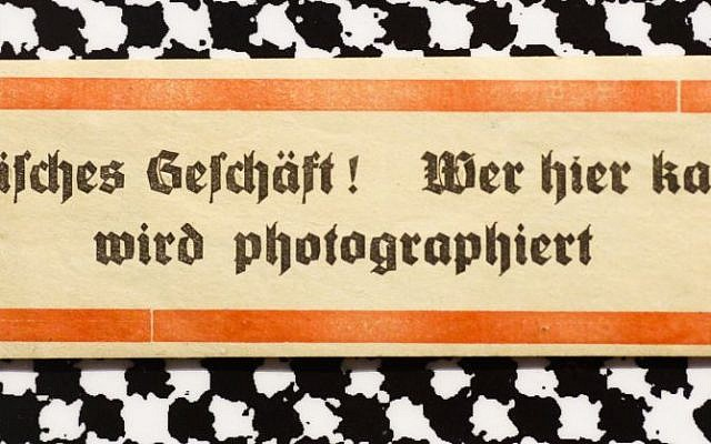 A sticker from around 1938 reading: 'Jewish shop! Whoever buys here will be photographed' displayed at an exhibition of antisemitic and racist stickers at the Deutsches Historisches Museum in Berlin, Germany, April 19, 2016. (AP Photo/Markus Schreiber)