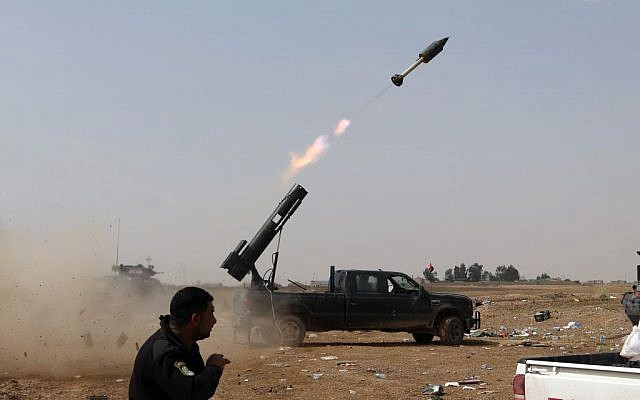 In this March 30, 2015, file photo, Iraqi security forces launch a rocket against Islamic State extremist positions during clashes in Tikrit, 130 kilometers (80 miles) north of Baghdad, Iraq. (AP/Khalid Mohammed)
