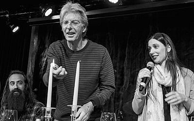 Phil Lesh lights the candles as Jeannette Ferber, a cantorial soloist at Berkeley's Renewal congregation Chochmat HaLev, sings the blessing, and guitarist Ross James looks on, at a Passover seder, April 2016. (© Bob Minkin Photography / www.minkinphotography.com via JTA)