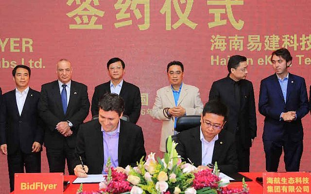 (Foreground L to R) Asaf Gendler, CEO of Israeli start-up Bidflyer, signs a partnership agreement with Kevin Yu, COO of Hainan Eco-Tech Group (Courtesy)