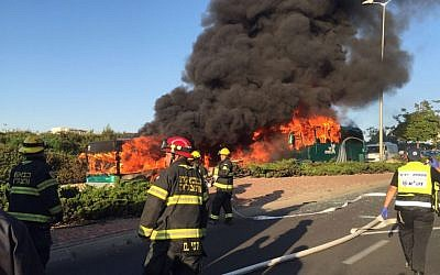 Firefighters look on as two buses burn in Jerusalem. Police launched an investigation into the incident, April 18, 2016. (Israel Police)