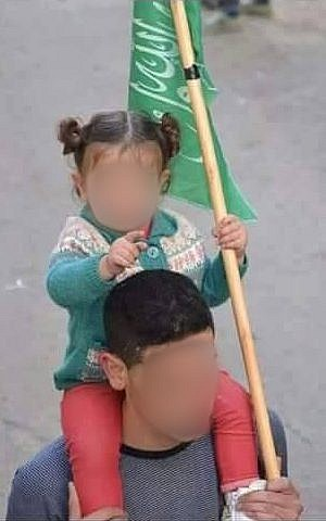 In an undated photo, the man named by Hamas as the person responsible for the April 18 bus bombing in Jerusalem holds a Hamas flag and carries an infant during a rally. He died of wounds sustained in the terror attack on April 20, 2016. (Courtesy)