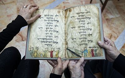 In this photo taken Wednesday, April 13, 2016, Eli and Shuli Barzilai holds a copy of the Birds' Head Haggadah in their home in Jerusalem.  (AP/Dan Balilty)
