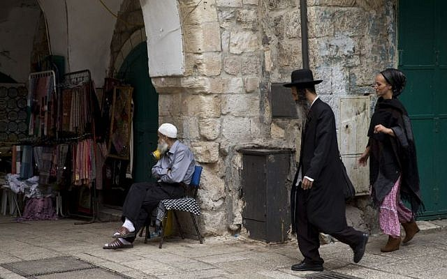 In this Friday, Oct. 9, 2015 file photo, a Jewish couple walk past a Palestinian man in the old city in Jerusalem. (AP Photo/Ariel Schalit, File)