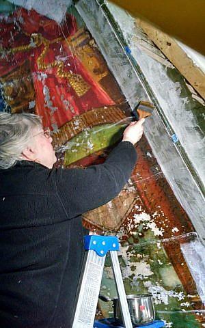 Constance Silver carefully restoring the Lost Shul Mural in Burlington, Vermont (courtesy)