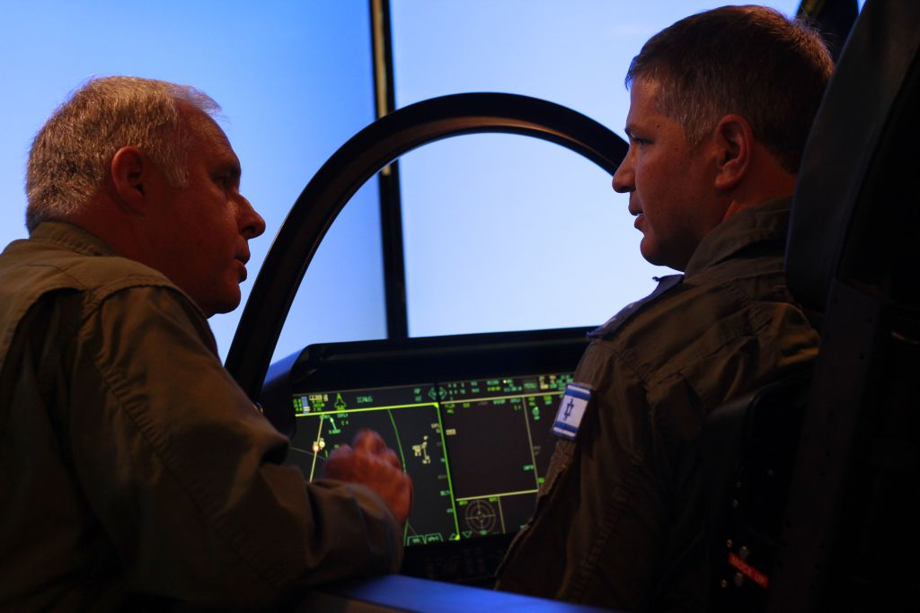 F-35 chief test pilot Alan Norman, left, speaks with pilot and Likud MK Yoav Kish in an F-35 simulator during a conference at Tel Aviv's Hilton Hotel on April 3, 2016. (Judah Ari Gross/Times of Israel)