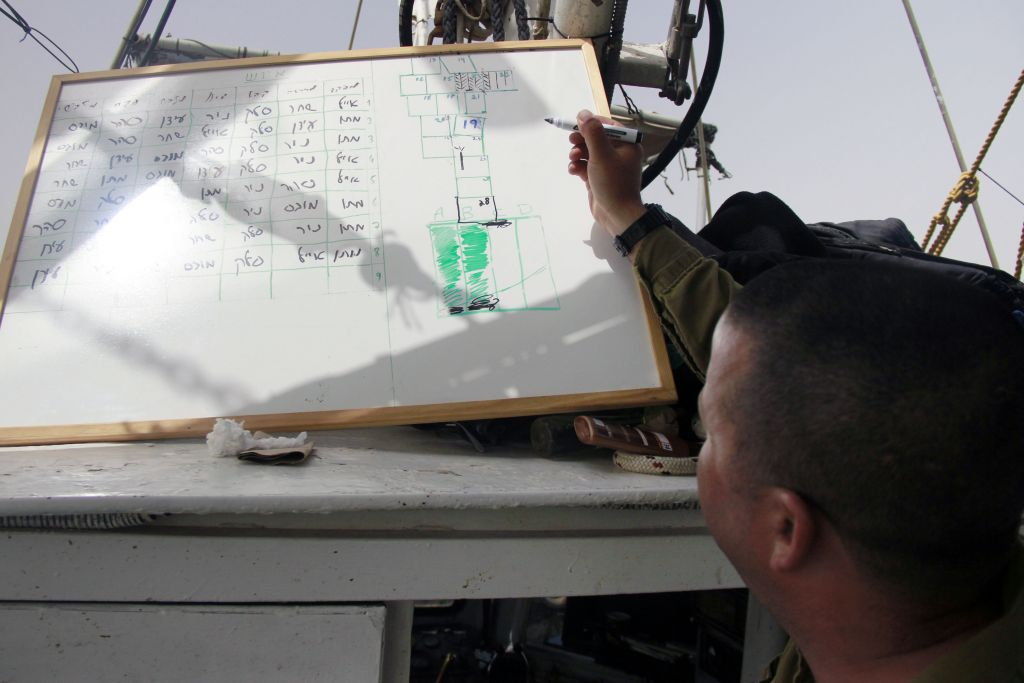 Maj. Matan Bar reviews the work that has already been done and marks off what areas still need to be checked in the search for missing pilot Lt. Yakir Naveh, whose plane crashed in the Sea of Galilee in 1962, on April 6, 2016. (Judah Ari Gross/Times of Israel)