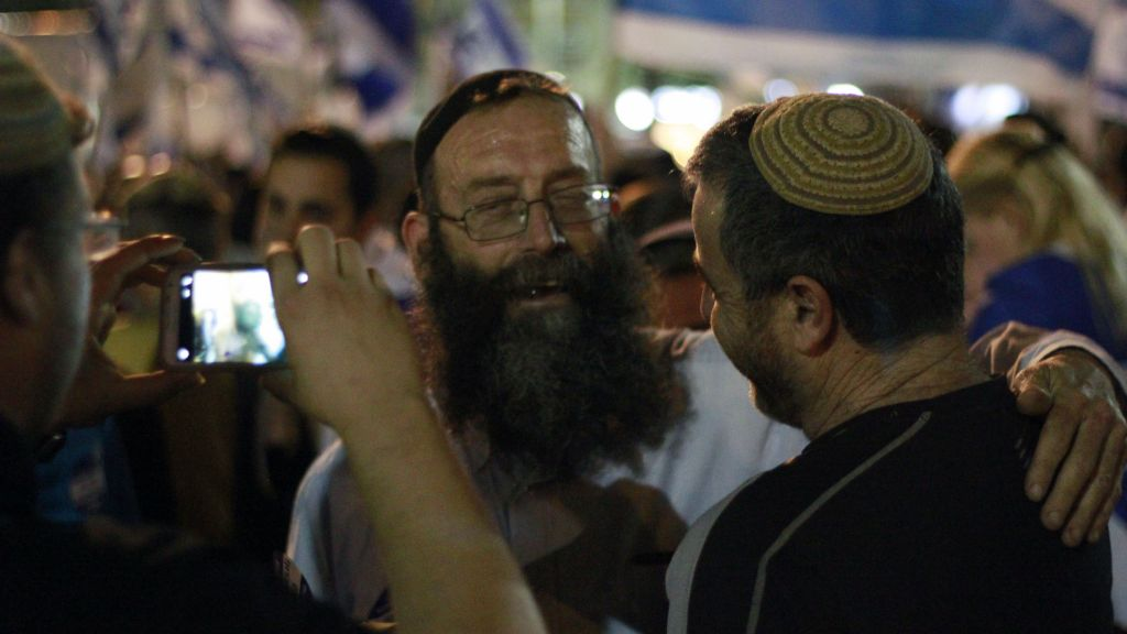 Jewish extremist activist Baruch Marzel takes a photograph with a fan during a rally in Tel Aviv on April 19, 2016 to support Elor Azria, an Israeli soldier recently charged with manslaughter after shooting a prone and wounded Palestinian assailant in the head. (Judah Ari Gross/Times of Israel)