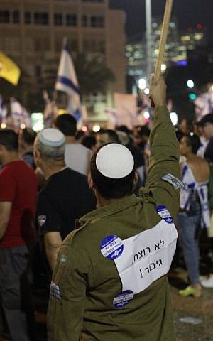 A man with a sign on his shirt reading, 'Not a murderer, a hero,' holds an Israeli flag sign during a rally in Tel Aviv on April 19, 2016 to support Elor Azria, an Israeli soldier recently charged with manslaughter after shooting a prone and wounded Palestinian assailant in the head. (Judah Ari Gross/Times of Israel)
