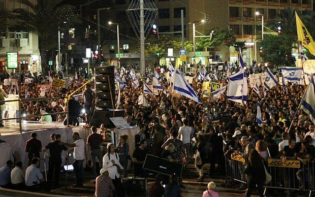 Israeli citizens hold Israeli flags and banners during a rally in Tel Aviv on April 19, 2016 to support Elor Aazria, an Israeli soldier recently charged with manslaughter after shooting a prone and wounded Palestinian assailant in the head. (Judah Ari Gross/Times of Israel)
