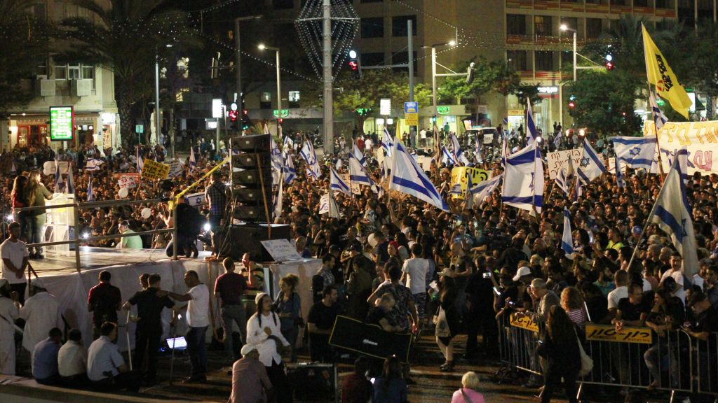 Israeli citizens hold Israeli flags and banners during a rally in Tel Aviv on April 19, 2016 to support Elor Azria, an Israeli soldier recently charged with manslaughter after shooting a prone and wounded Palestinian assailant in the head. (Judah Ari Gross/Times of Israel)