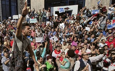 "Egyptians shout slogans against Egyptian President Abdel-Fattah el-Sissi during a protest against the decision to hand over control of two strategic Red Sea islands to Saudi Arabia in front of the Press Syndicate, in Cairo, Egypt, Friday, April 15, 2016. Arabic reads, ""Awad sold his land"" and ""Red Sea islands Sanafir and Tiran are Egyptian."" (AP Photo/Amr Nabil)"