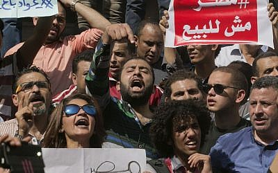 Egyptians shout slogans against Egyptian President Abdel-Fattah el-Sissi during a protest against the decision to hand over control of two strategic Red Sea islands to Saudi Arabia in front of the Press Syndicate, in Cairo, Egypt, Friday, April 15, 2016. The signs in Arabic read, 'Awad sold his land' and 'Egypt is not for sale.' (AP Photo/Amr Nabil)