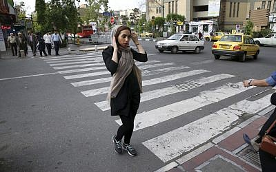 An Iranian woman adjusts her headscarf while crossing a street in downtown Tehran, Iran, Tuesday, April 26, 2016. (AP Photo/Vahid Salemi)