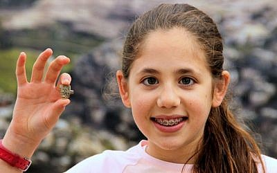 This image released by the Ir David Foundation - City of David on Tuesday, April 19, 2016 shows Neshama Spielman with an ancient Egyptian amulet dating back more than 3,200 years to the days of the Pharaohs discovered by the 12-year-old Israeli girl. Spielman and her family took part in the Temple Mount Sifting Project, an initiative to sort through earth discarded from the area of the biblical temples in Jerusalem. (Adina Graham, Ir David Foundation - City of David via AP)