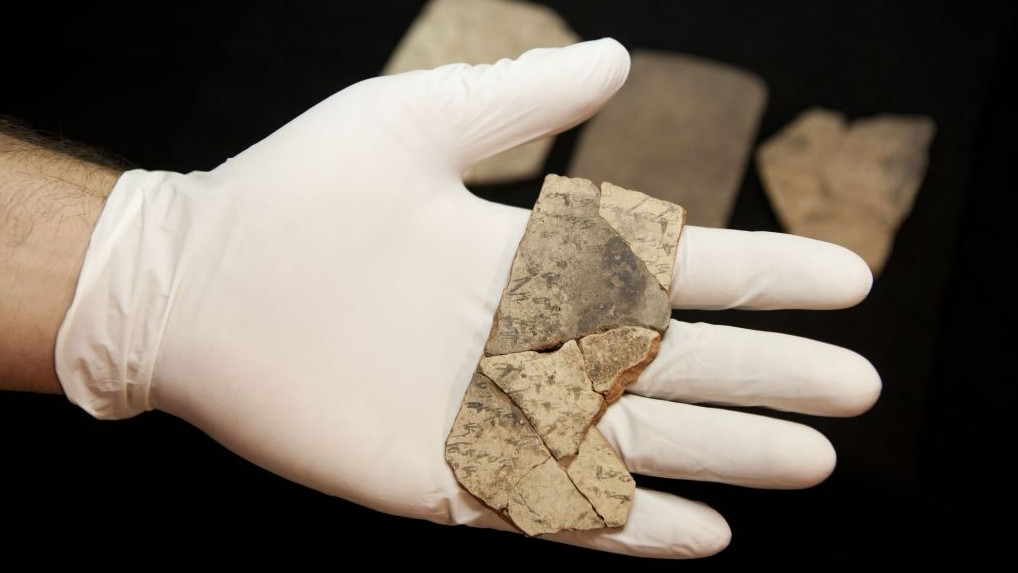Illustrative image of letters inscribed on pottery, known as ostraca, which were unearthed in the excavation of a fort in Arad, Israel, are seen in the Israel Museum in Jerusalem, April 12, 2016. (AP/Dan Balilty)