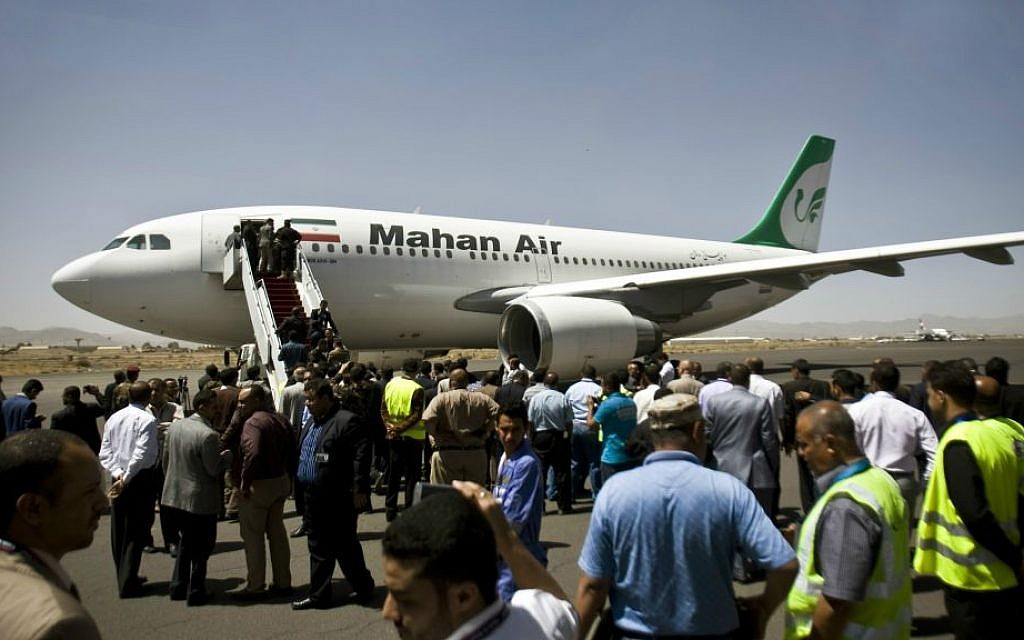 In this March 1, 2015 file photo, Yemeni airport, security and transportation officials greet a plane from the Iranian private airline Mahan Air after it lands in Sanaa, Yemen. (AP Photo/Hani Mohammed, File)