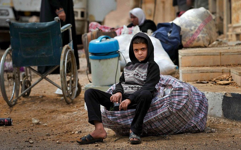In this April 14, 2016 image, a Syrian boy waits as his family loads their belongings onto a bus in the town of Palmyra in the central Homs province, Syria. (AP Photo/Hassan Ammar)