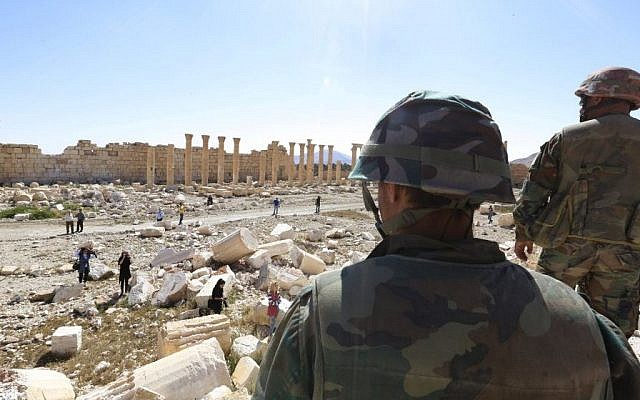 In this picture taken Friday, April 1, 2016, soldiers look over damage at the historical Bel Temple in the ancient city of Palmyra in the central city of Homs, Syria.  (AP)