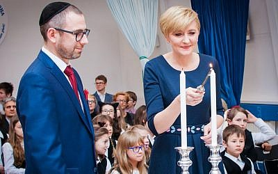 Polish First Lady Agata Duda lights candles with Pawlak during a visit to the school (courtesy)