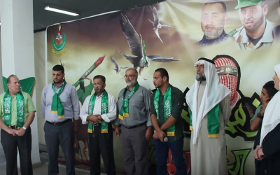 Screen shot taken from a speech by Dr. Imad al-Barghouthi at Hamas rally at al-Quds University in Jerusalem in October 2014.  He is standing on the far left, and is flanked by a poster honoring Hamas' military wing.  (screen capture: YouTube)