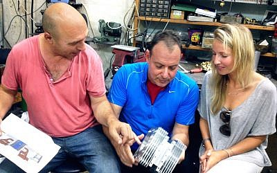 (L to R) Shaul Yaakoby, CTO and Inventor, Gal Fridman, CMO and Maya Gonik, Head of Business Development check out an Aquarius engine (Courtesy)