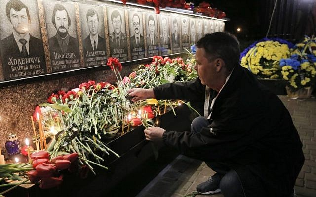 A man lays flowers to commemorate victims of the Chernobyl nuclear disaster, during a ceremony at the memorial to Chernobyl workers and firefighters in the town of Slavutych, Ukraine, early Tuesday, April 26, 2016. (AP Photo/Efrem Lukatsky)